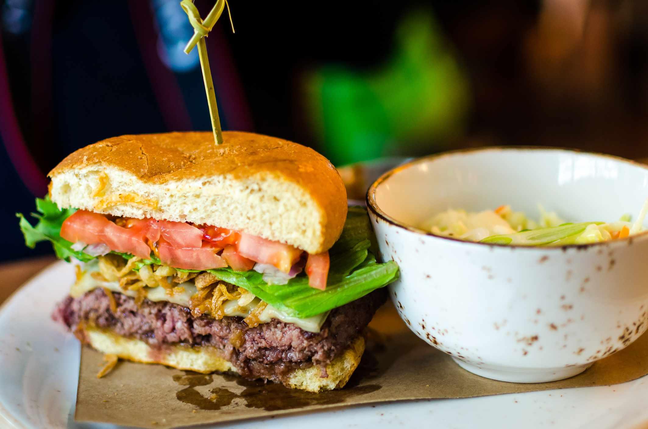 media hamburguesa de bisonte con un plato de ensalada de col al lado