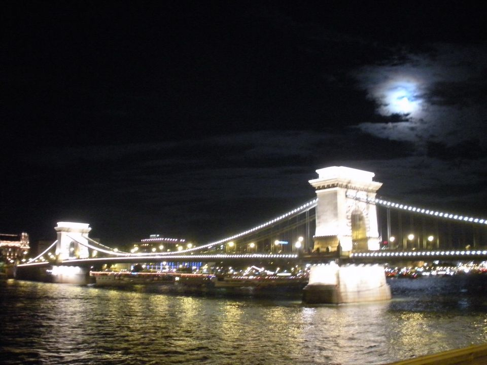 The Chain Bridge sparkles under a full moon over Budapest.