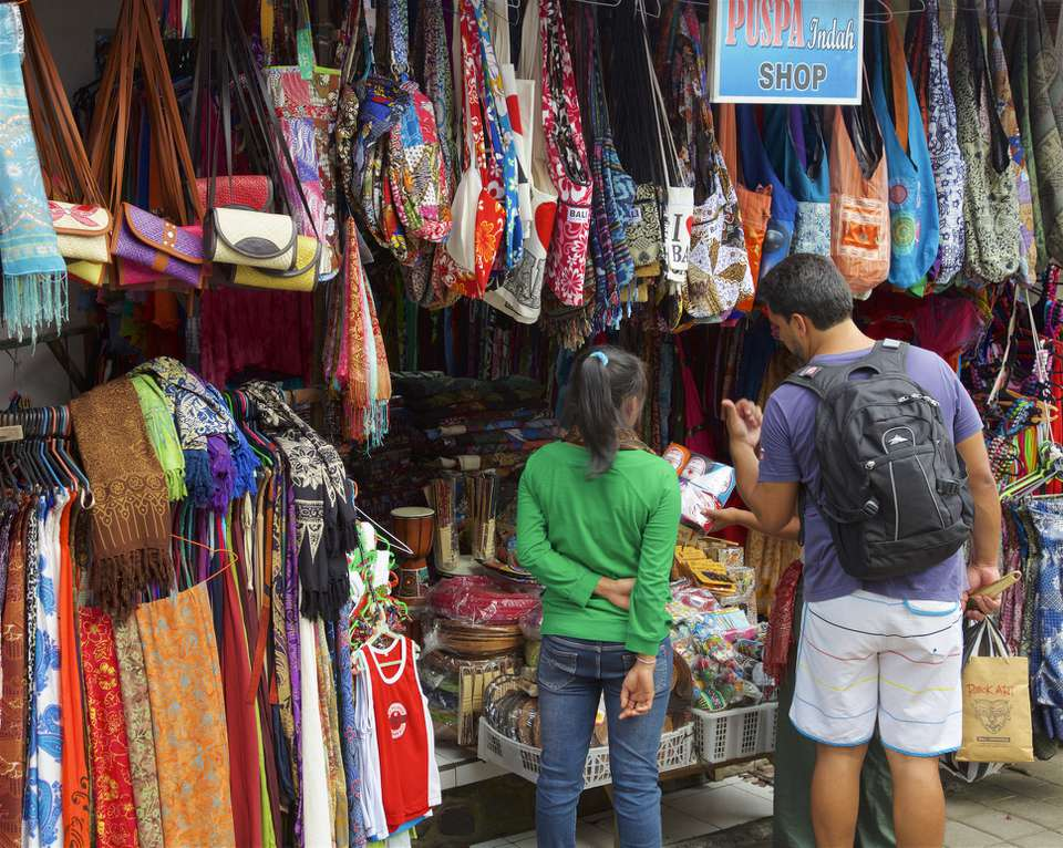 A tourist at a Bali market stall bargaining with shop attendant