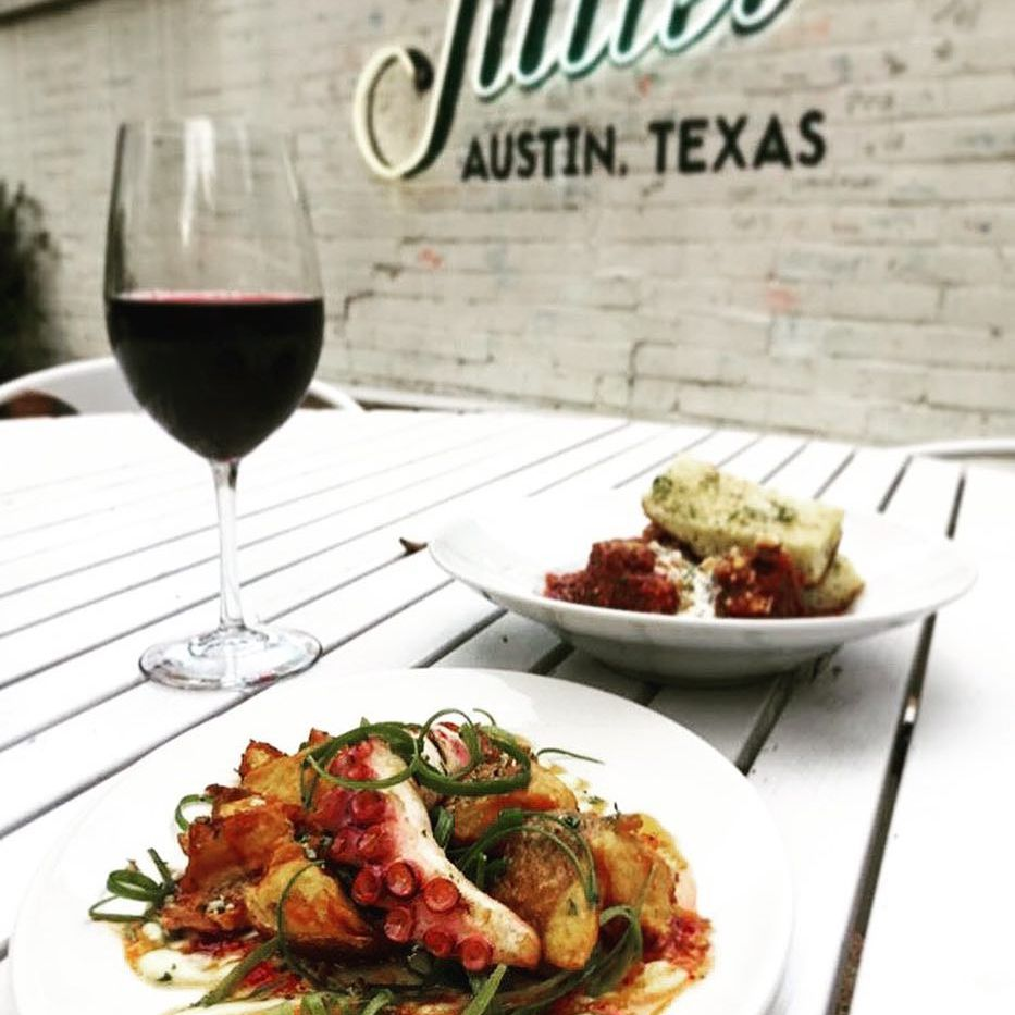 Wine and appetizers on a white table at Juliet in Austin, Texas.