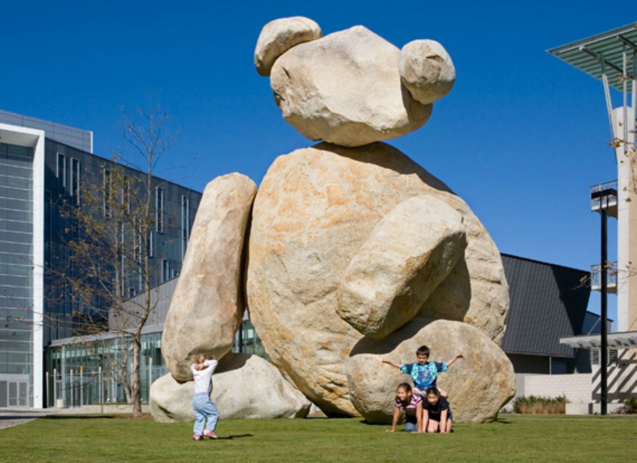 People posing in front of a large bear sculpture