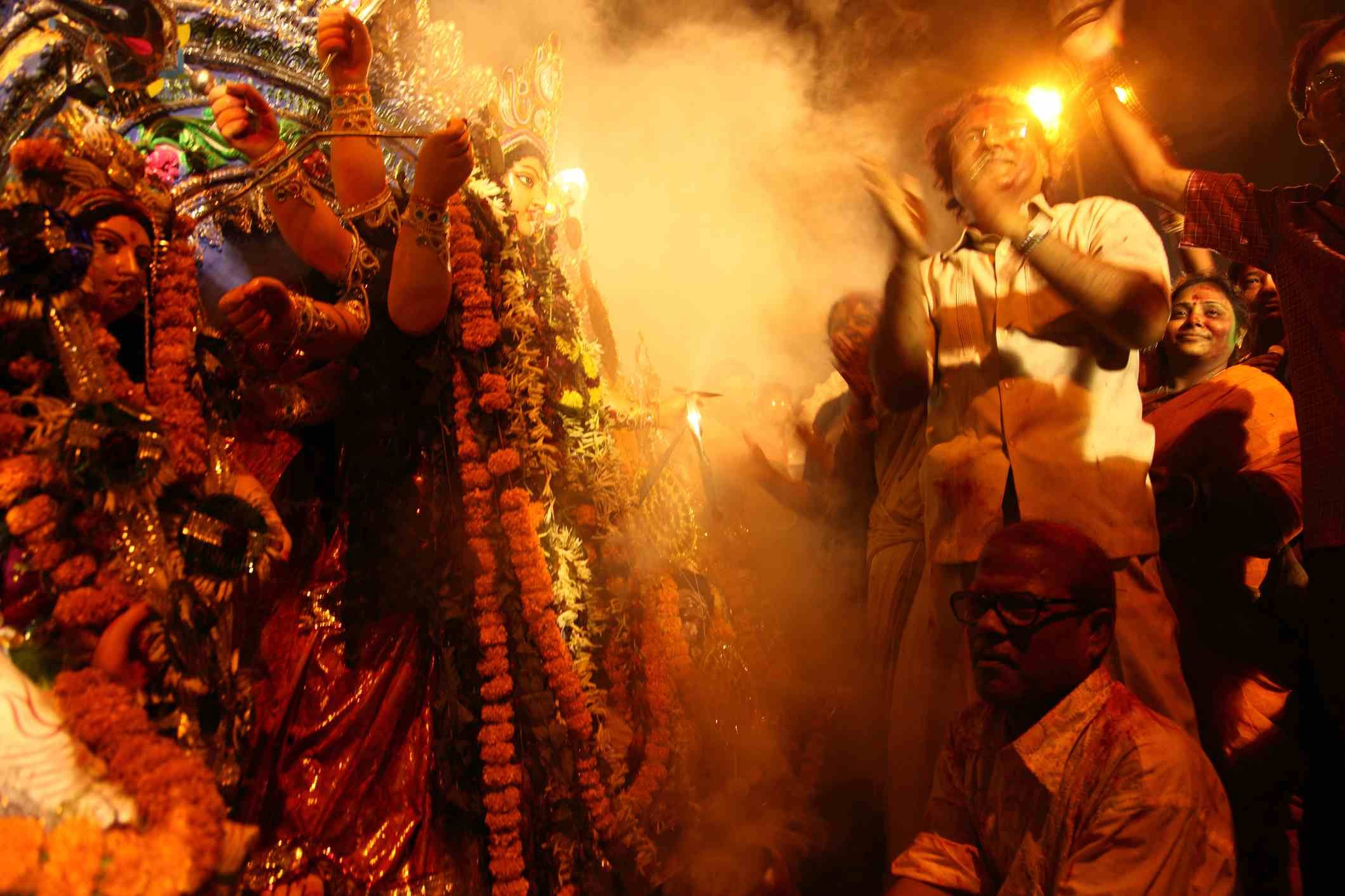 Devotees praying and dancing in-front of Durga idol before immersing in the river during Durga Puja festival