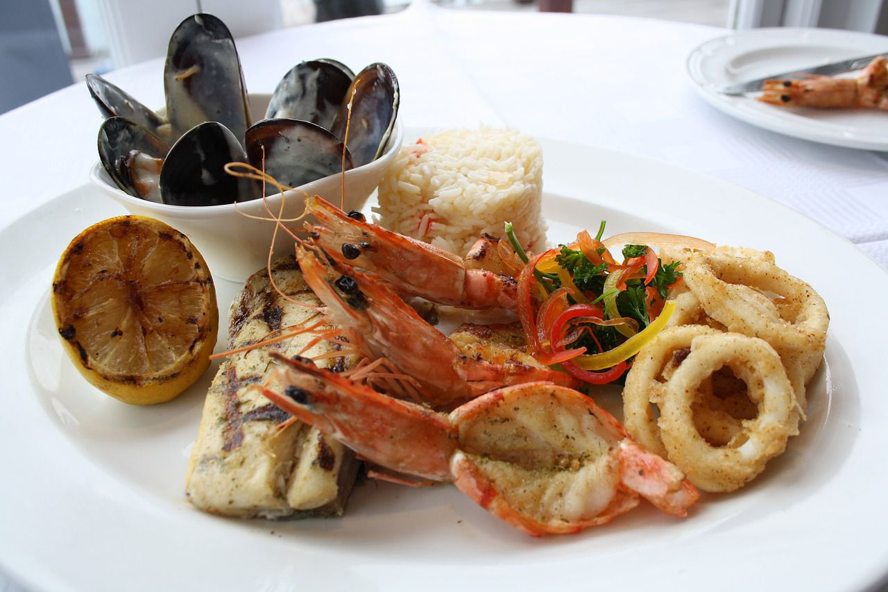 A plate with fried seafood, mussels and lemon