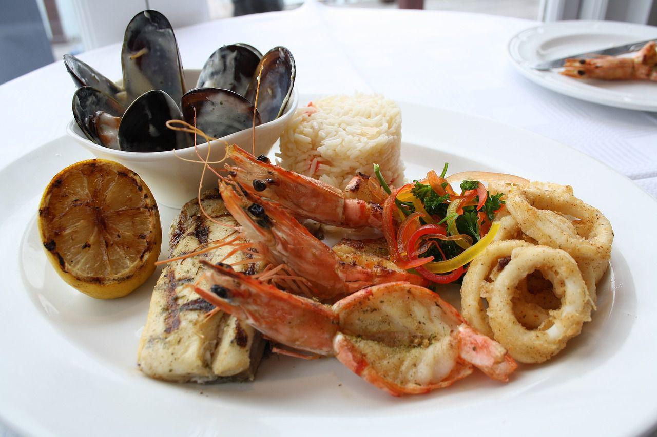 Un plato con mariscos fritos, mejillones y limón