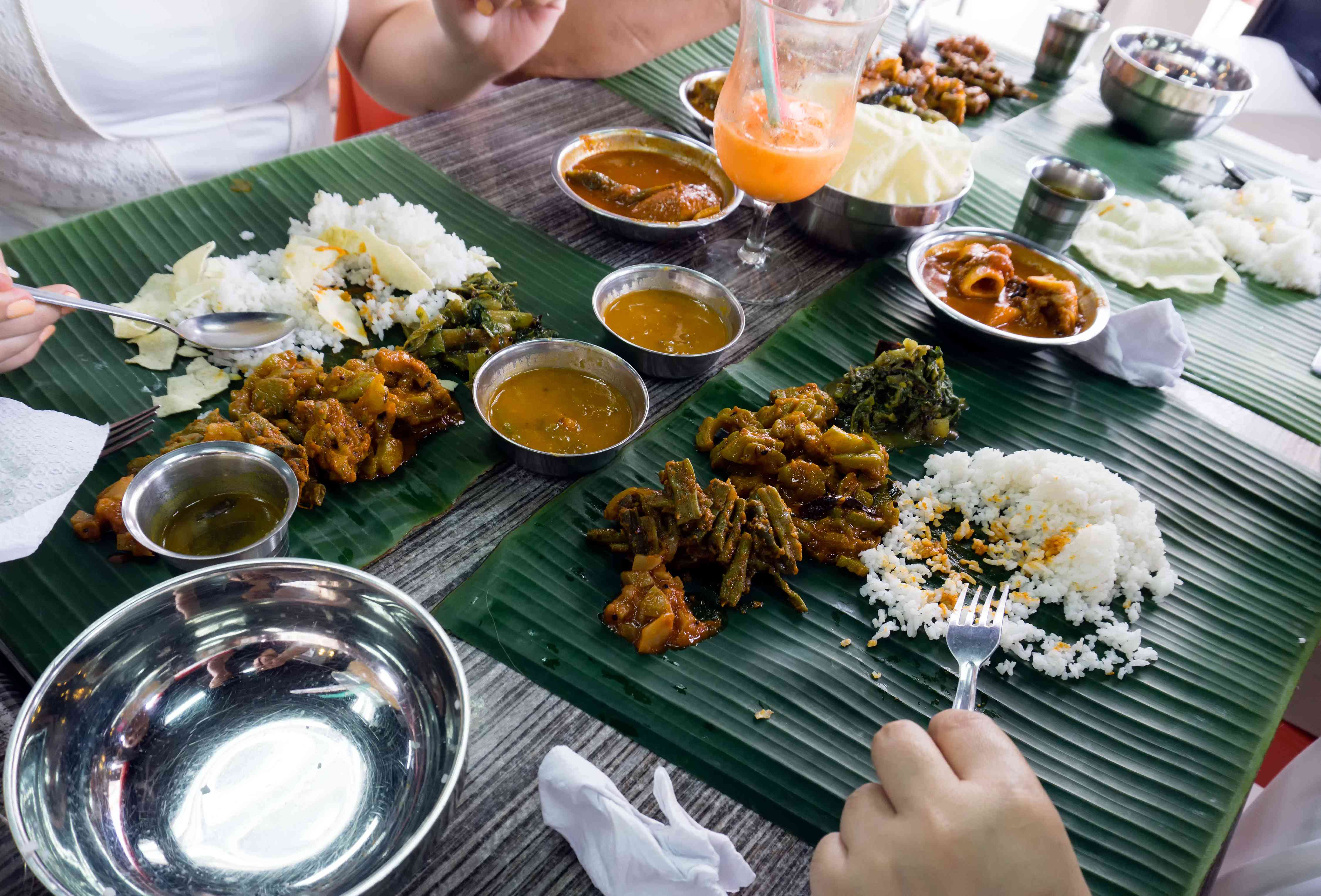 People eating Indian food and curry on a banan leaf