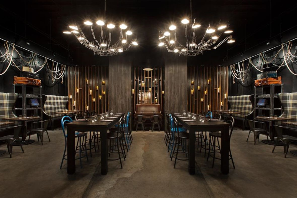 Dark intenriro of restaurant with wingback booths on the side walls and two large chandeliers