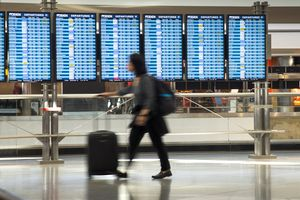 Passenger hurrying to departure gate in front of flight departure boards