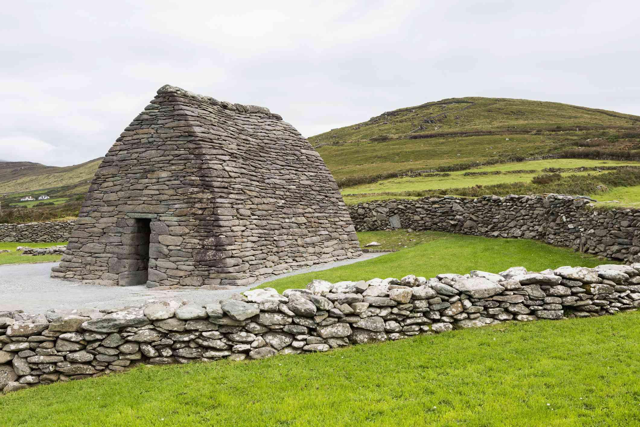 Gallarus Oratory stone church against green hills in Ireland