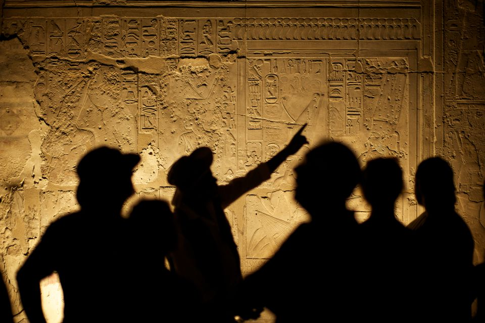 A group of tourists and their guide silhouetted against Egyptian hieroglyphs