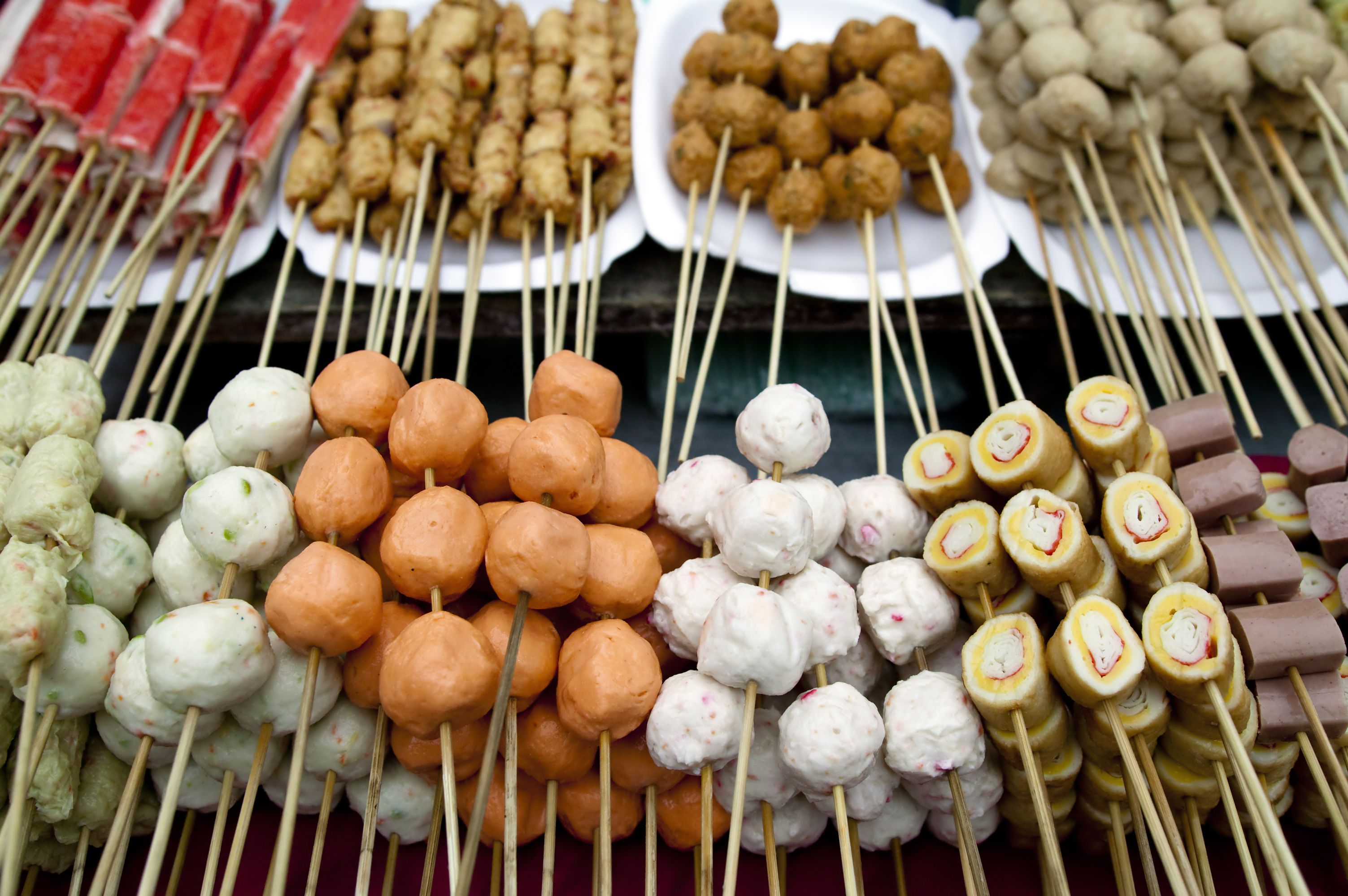traditional malaysian street food called lok lok or chinese fondue. the meat on the skewers is placed in the boiling water to cook and eaten on the spot
