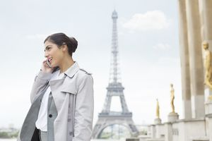 Businesswoman talking on cell phone by Eiffel Tower, Paris, France