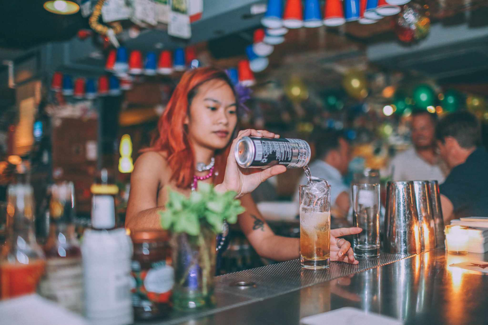 Woman pouring drink at busy bar