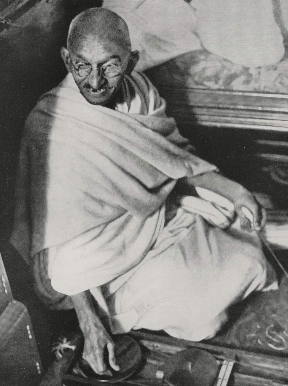 Mahatma Gandhi in robes sitting