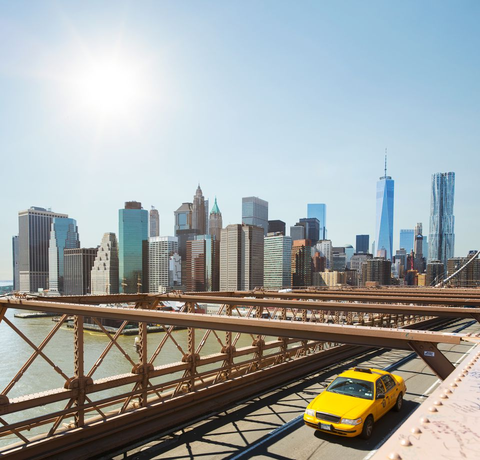 A yellow cab crossing the Brooklyn Bridge.