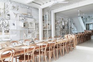 long wooden tables with chairs in an all white restaurant dining room