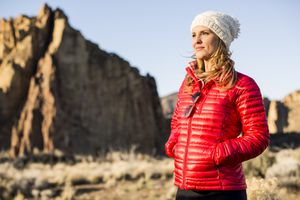 blonde woman in a white hat and red jacket in front of a large, out-of-focus rock formation