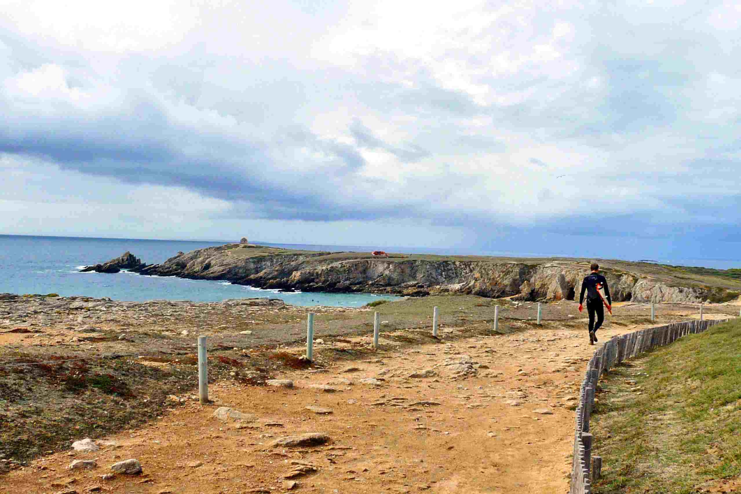 A surfer walks a trail with his board on the Quiberon Peninsula in Southern Brittany