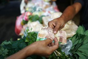 A customer, bottom, hands Indonesian rupiah banknotes to a vegetable vendor
