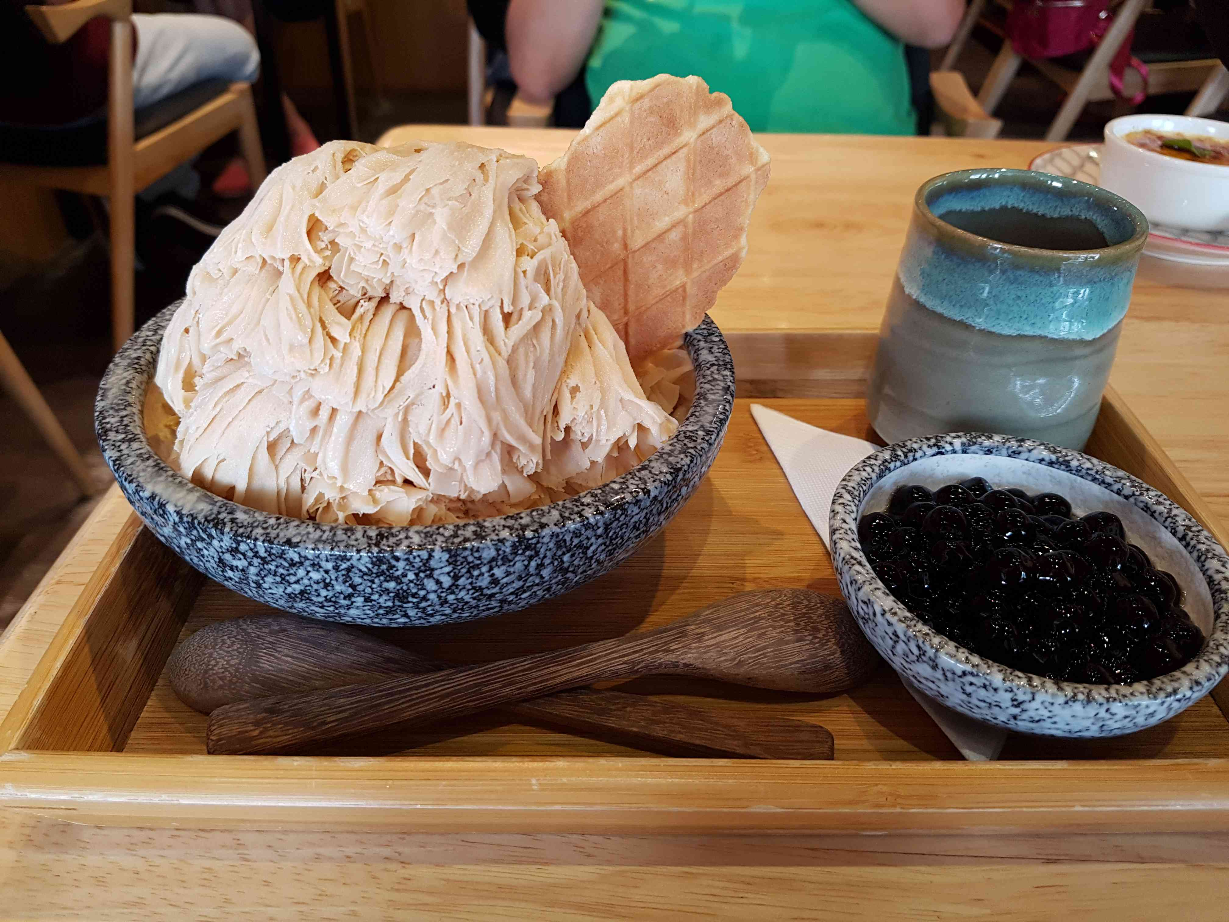 milk-tea flavored xuehuabing in a stone bowl with a side bowl of tapioca pearls