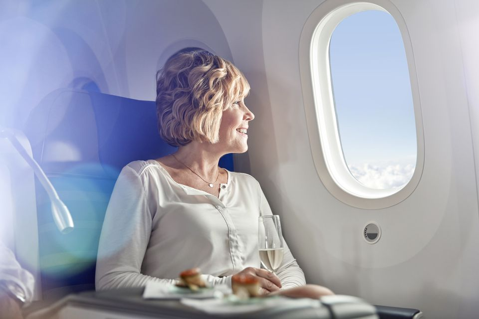Smiling woman drinking champagne, traveling first class, looking out airplane window
