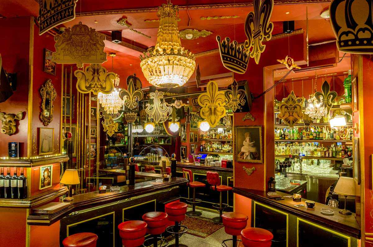 To Noel bar in Athens with red stools by the bar, several chandeliers, red walls and paper crowns suspended from the ceiling