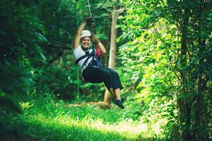 Woman zip lining through forest