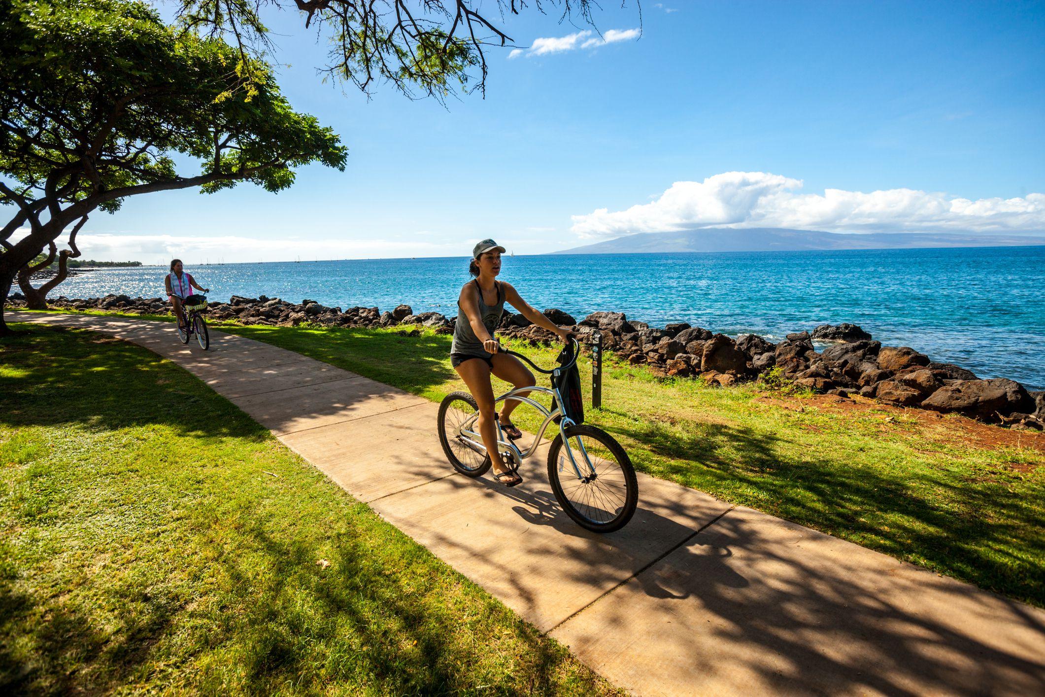 Women cycling along the beach, Maui