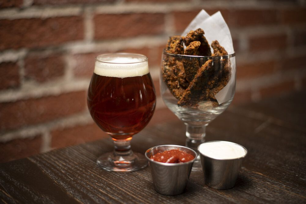 glass of beer and deep fried vegetables in a glass on a table with condiments