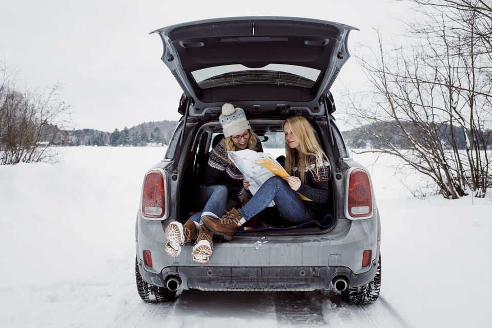 Two women reading a map in the open truck of a suv, parked on a snowy road