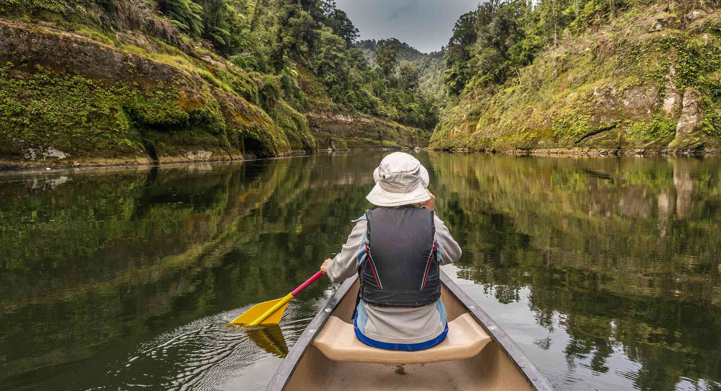person sitting in a canoe on a river surrounded by grassy cliffs