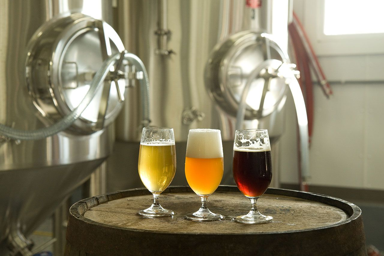 3 Beer glasses on an oak barrel, one class has a pale wheat colored liquid, one with a light orange, and one with a dark amber beer