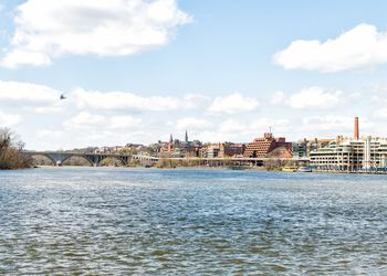 Cityscape, skyline view of Potomac river, Georgetown waterfront park in Washington, DC, District of Columbia, water waves, helicopter flying on sunny spring day, Whitehurst freeway, blue sky ,clouds