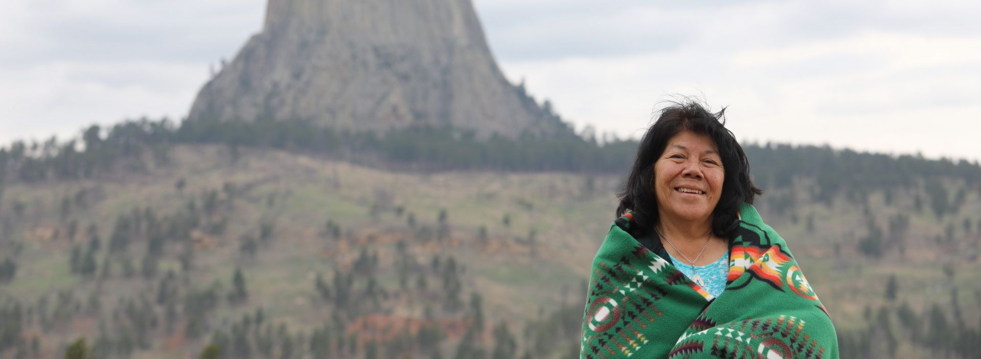 Indigenous woman wearing a blanket and smiling in front of the Devil's Tower natural monument in Wyoming