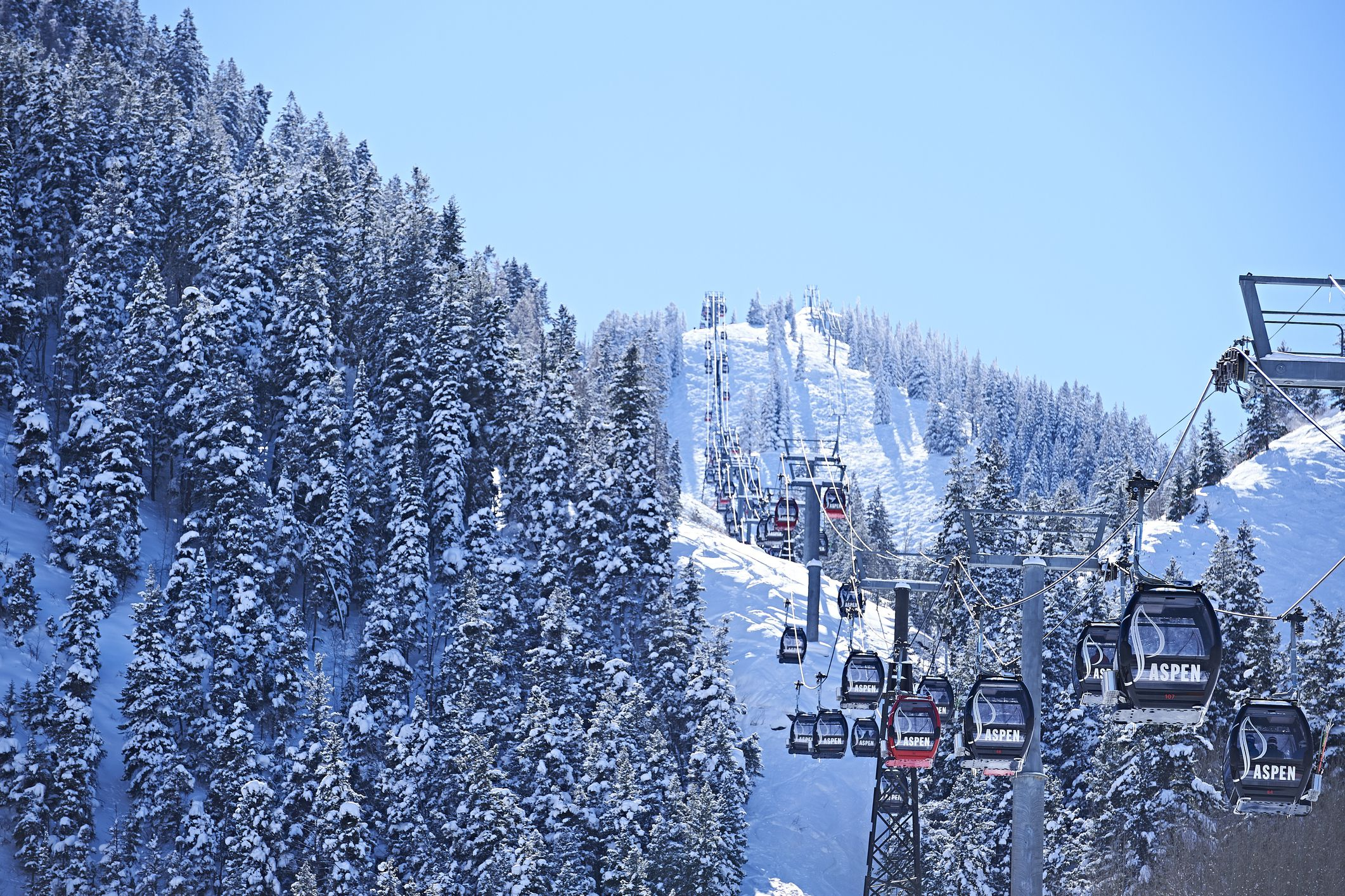 Cable car moving up over forested snow covered mountains in Aspen