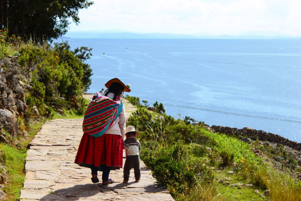 Mother and child in traditional clothing walking along Lake Titicaca