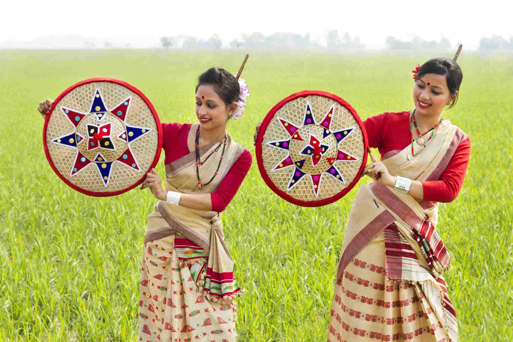 Bihu women holding jaapis.