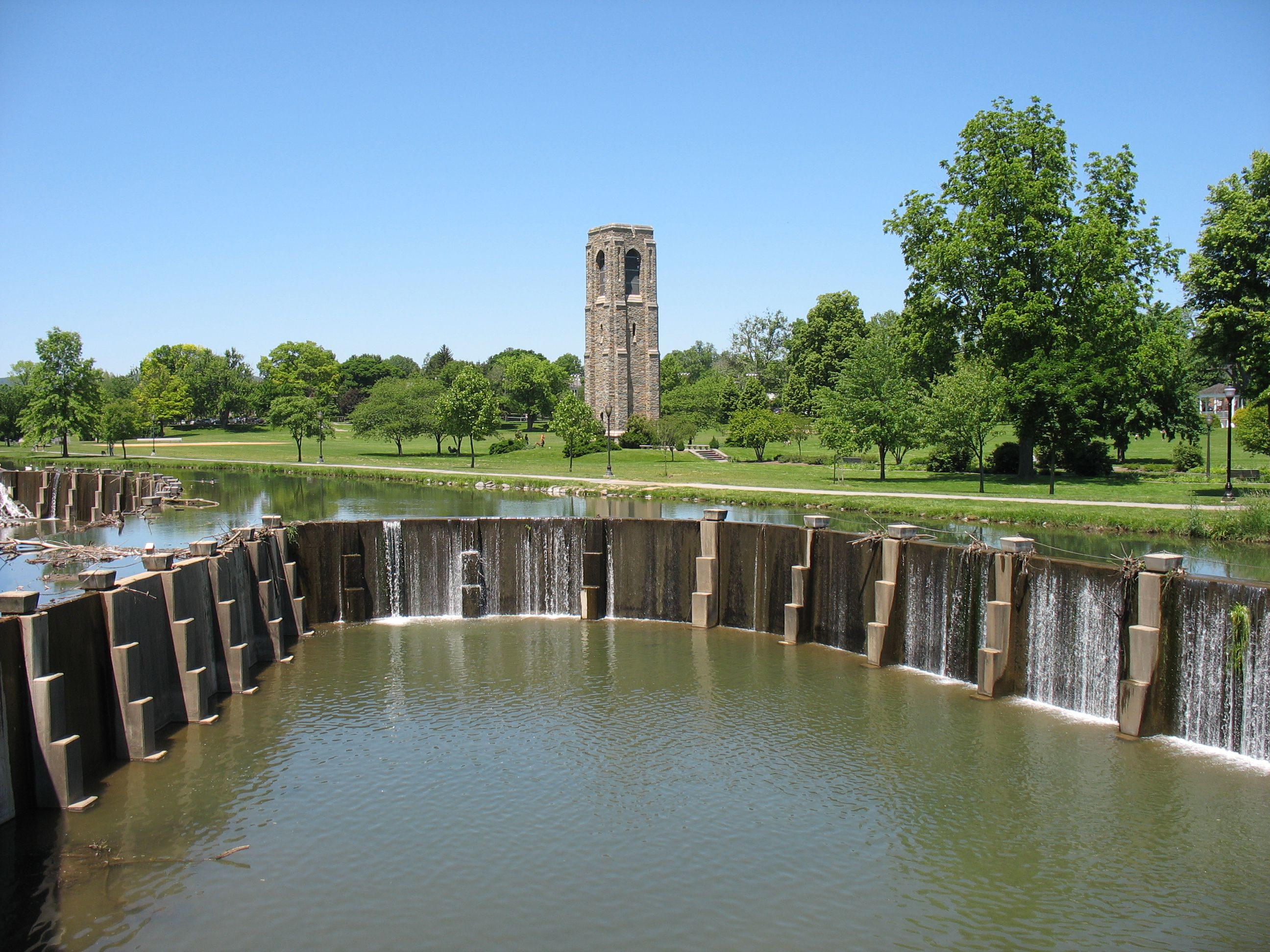 View of a pond and man-made waterfalls and a tower in Baker Park