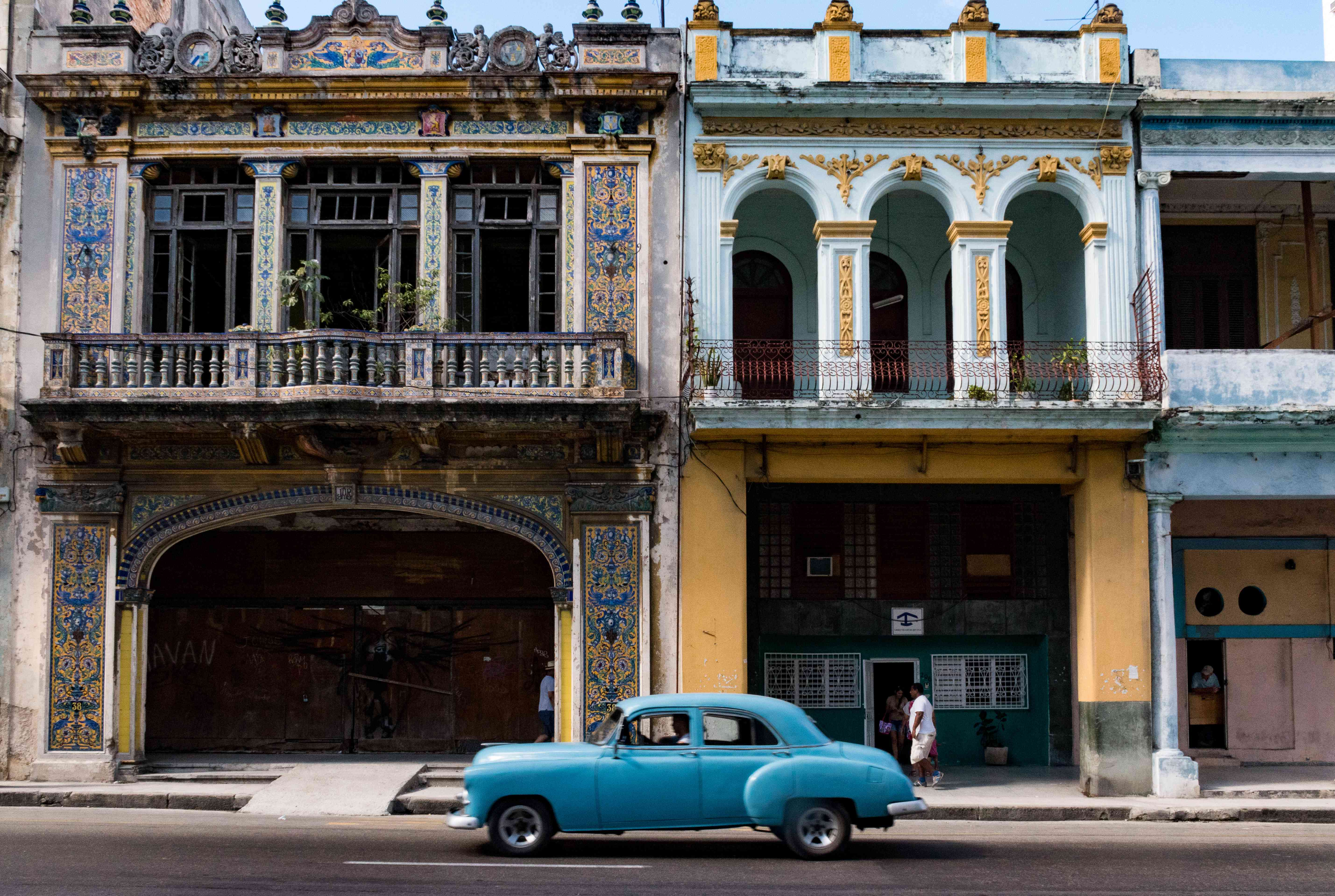 A classic car driving by an ornate building in Old Havanna