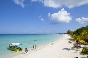 People walking on white sand beach near clear blue water with covered green and yellow boat in the foreground at Negril, Jamaica.