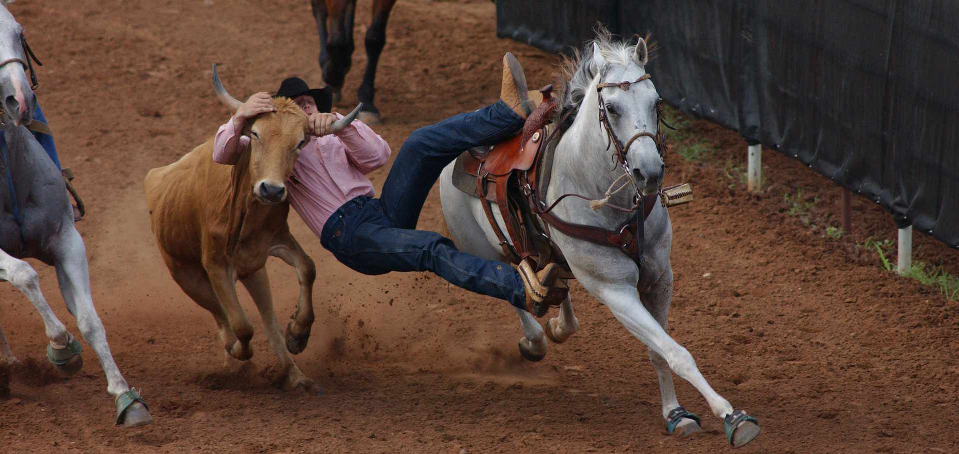 Oklahoma Rodeos with man falling off mustang