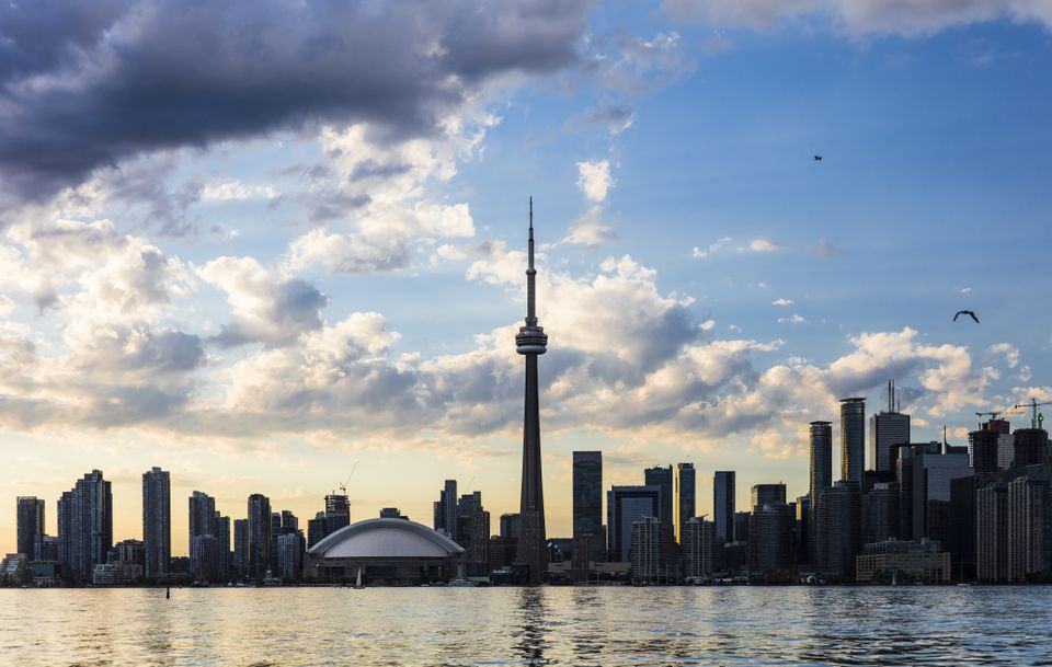 View of the Toronto skyline with a blue cloudy sky behind it