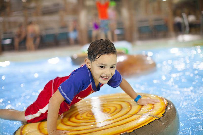 Boy riding raft in water park