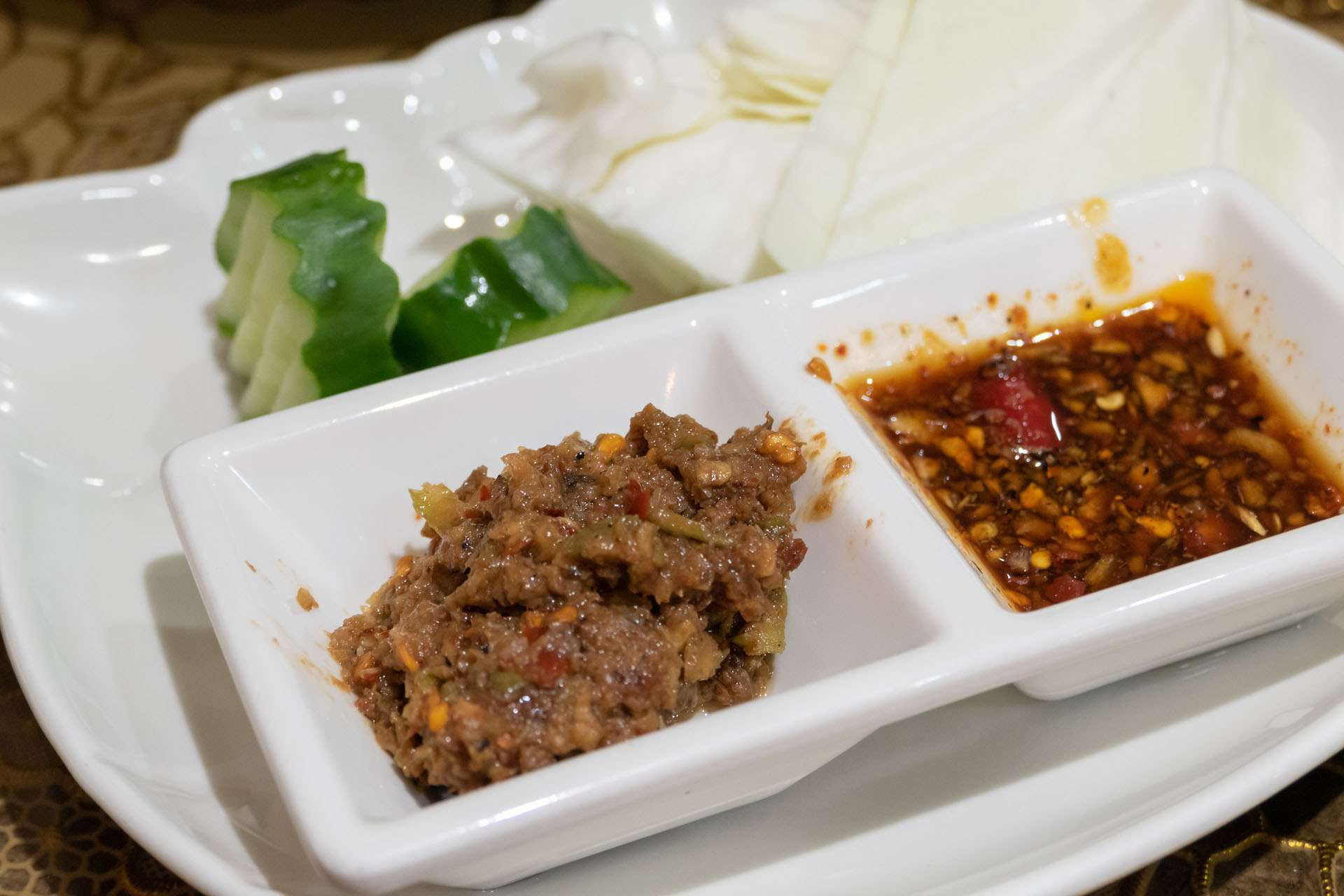 sauce dish with Ngapi on a plate with cucumber slices