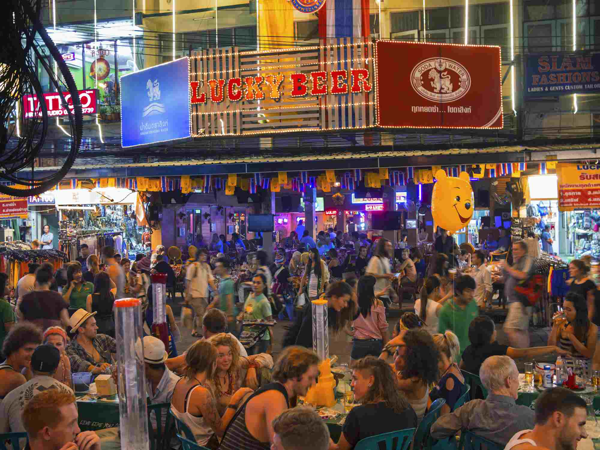 Travelers and vendors on Khao San Road at night