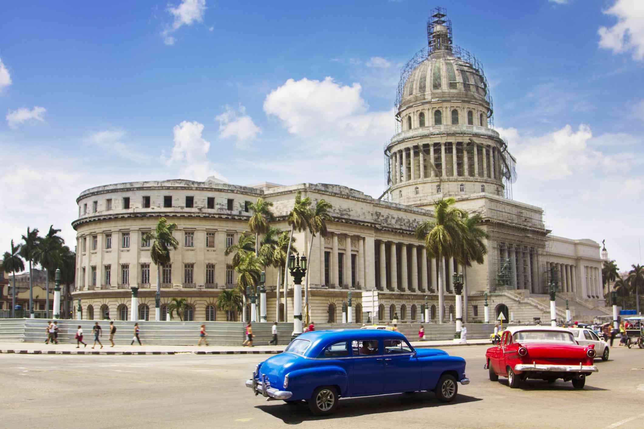 Vintage cars drive past Capitolio, Havana, Cuba