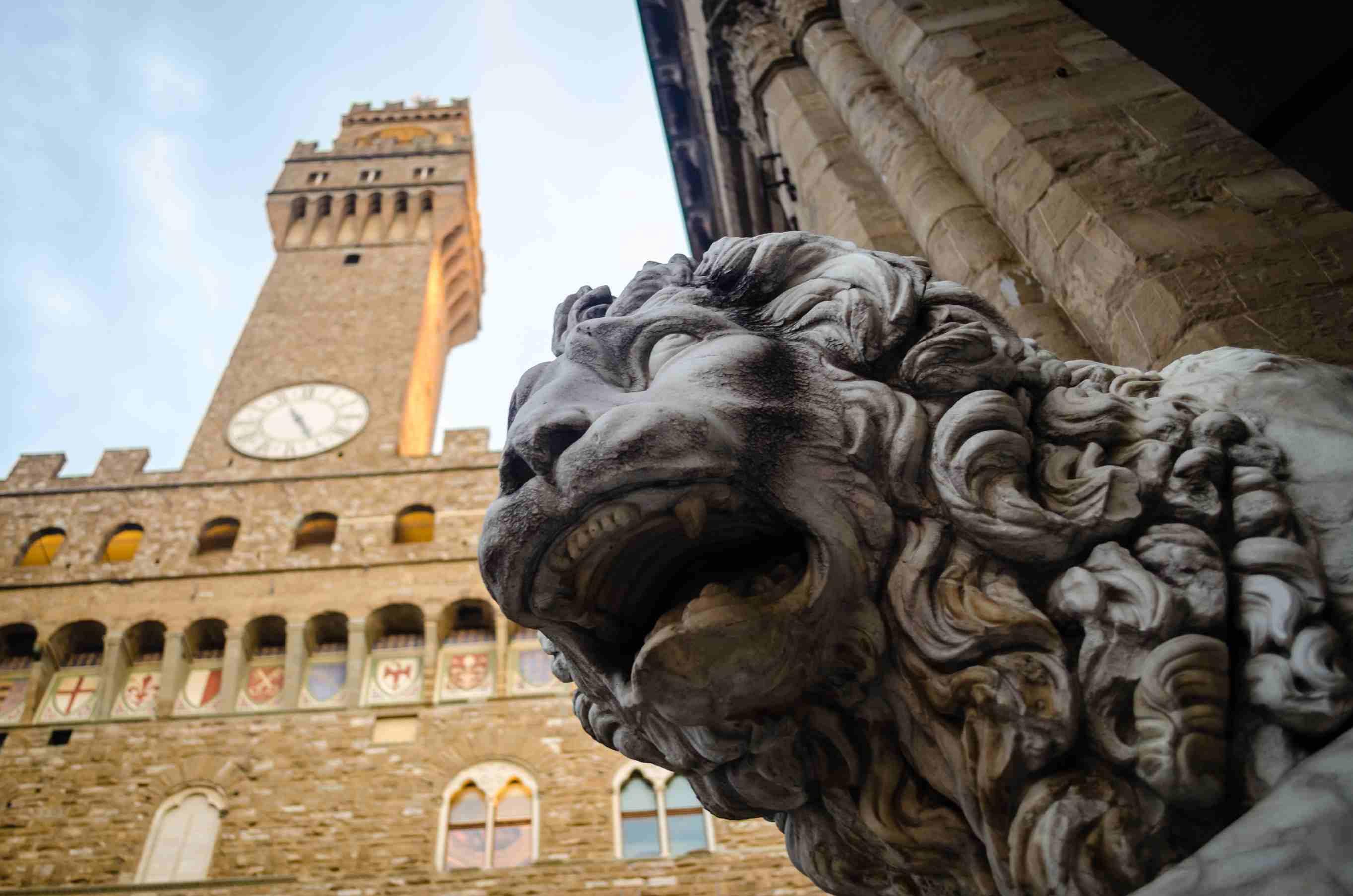 Estatua del León con el Palazzo Vecchio en Florencia, Italia