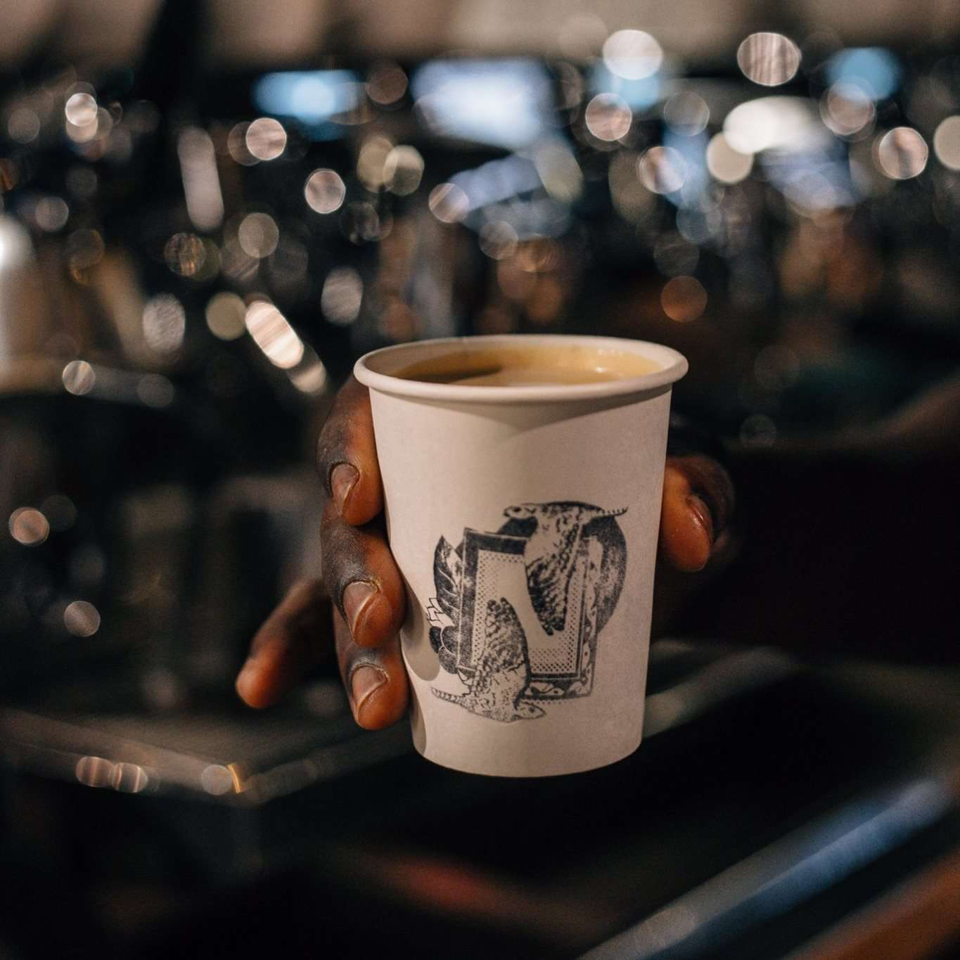 Dark skinned hand hoding a paper cup decorated with an ornate