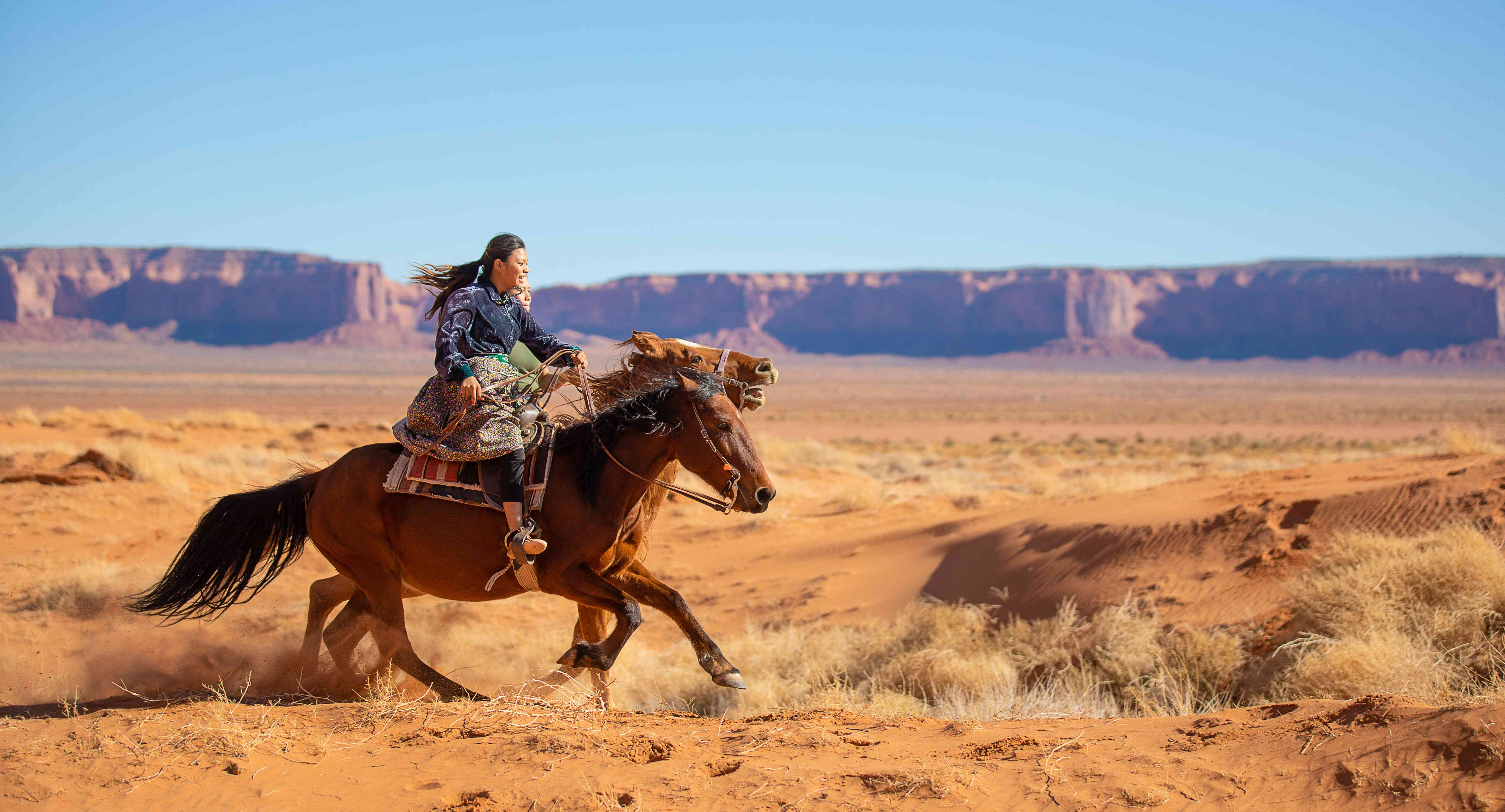 Navajo brothers galloping on horses in Arizona