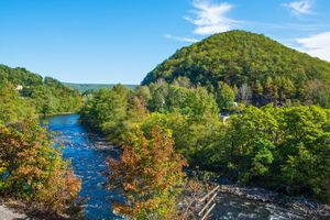 Scenic Lehigh River with a large hill to the right and a lot of green trees