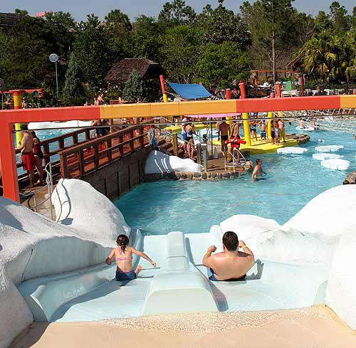 A father and daughter race down a small pair of slides.